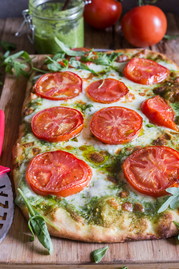 pesto pizza on a wooden board
