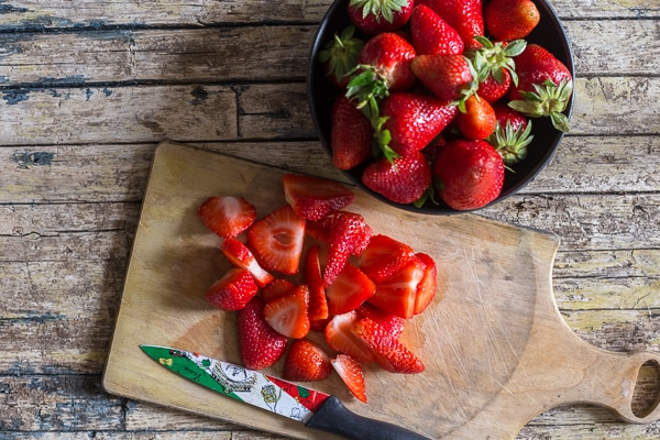 freezing strawberries slices on a board and whole in a bowl