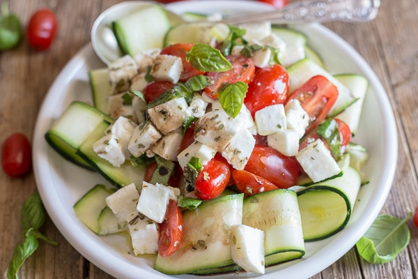 up close zucchini caprese salad on a white plate