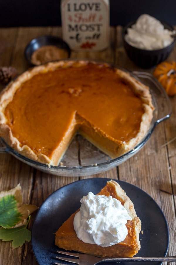 pumpkin pie in a glass dish and one slice on a black plate
