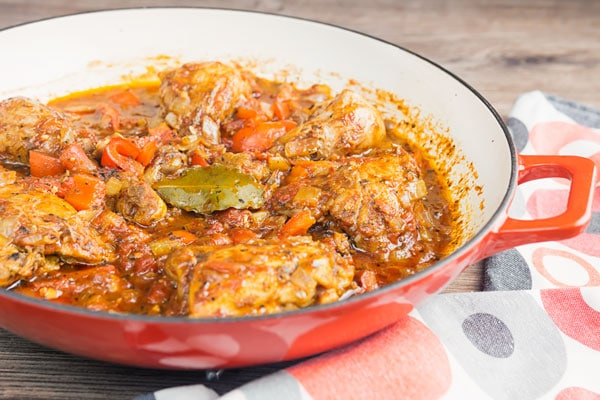 chicken cacciatore in a red and white skillet
