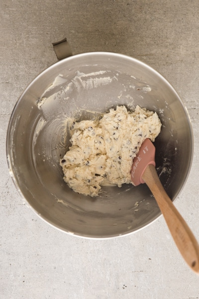 adding the chocolate chips to the creamed flour, butter and sugar mixture