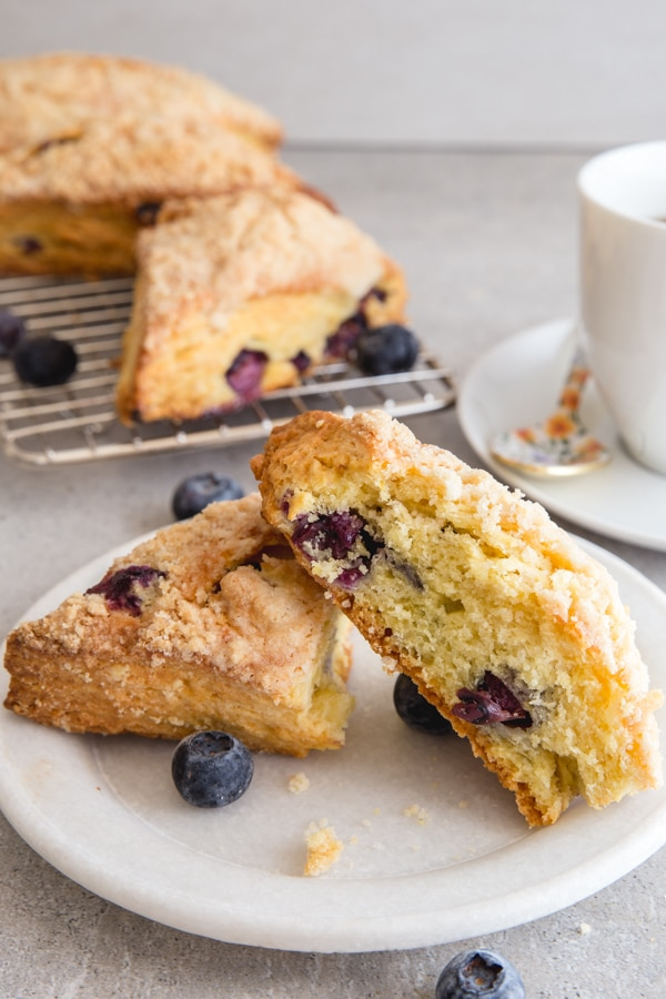 a cut blueberry scone on a white plate