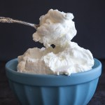stablilzed whipped cream in a blue bowl with a spoonful