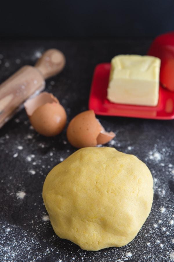 Italian pie crust on a black board with a rolling pin, empty egg shells and butter