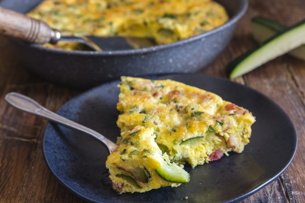 baked frittata a slice in a black plate with a forkful cut