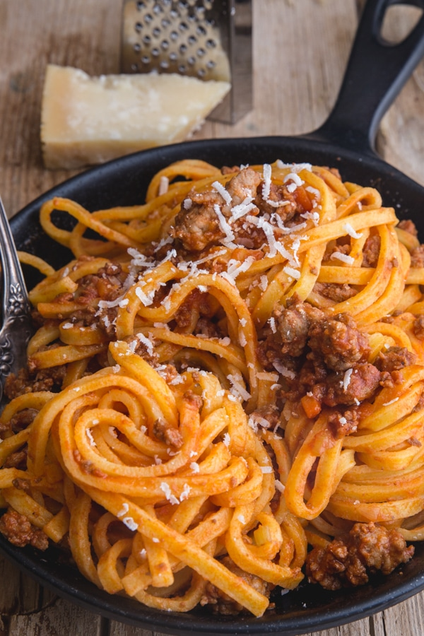 bolognese sauce with pasta and a sprinkle of parmesan cheese in a black pan