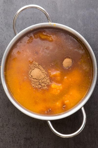 adding pumpkin butter ingredients to a pot