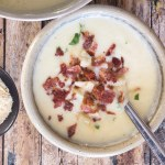 cauliflower soup in a white bowl with chopped bacon and parsley