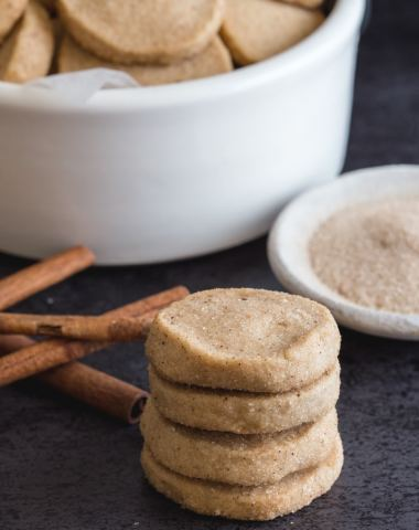 cinnamon shortbread cookies in a white bowl and 4 stacked with cinnamon in a small white bowl