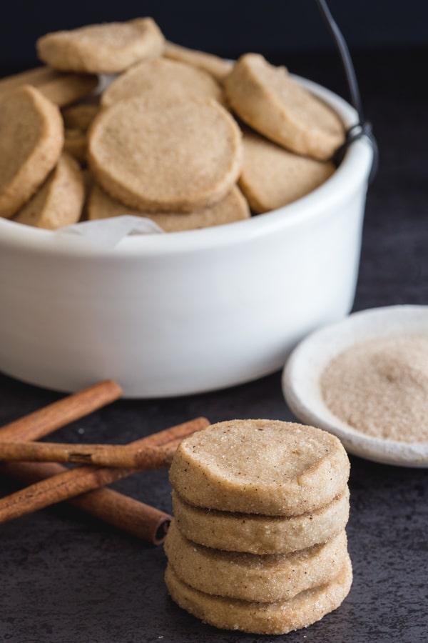 cinnamon shortbread cookies in a white bowl and 4 stacked with cinnamon in a small white bowl