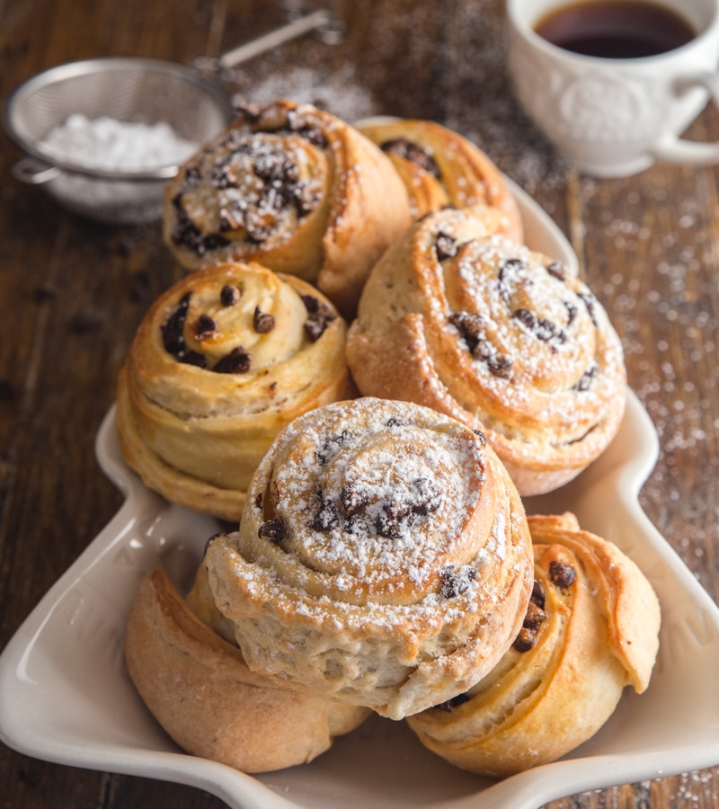 sweet buns on a white christmas tree plate with a cup of coffee and powdered sugar sifter