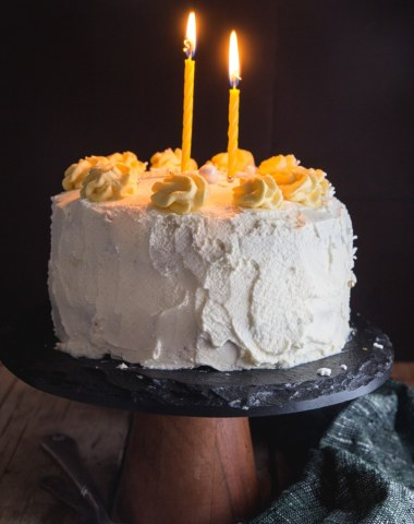 birthday cake on a black cake stand with two lit candles