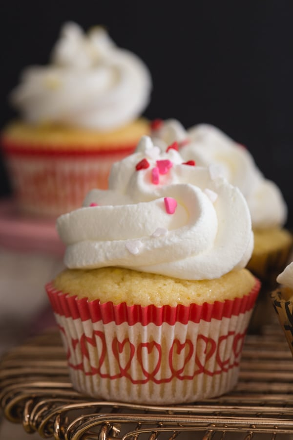 lemon cupcakes on a gold wire rack with one in the background on a small stand
