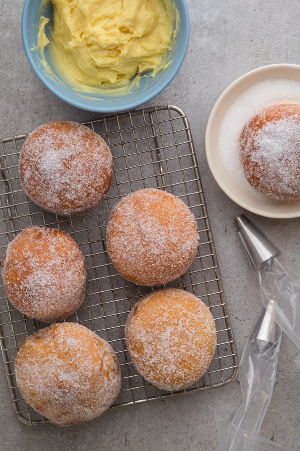 donuts on a wire rack one donut in a dish with sugar and pastry cream in a blue bowl