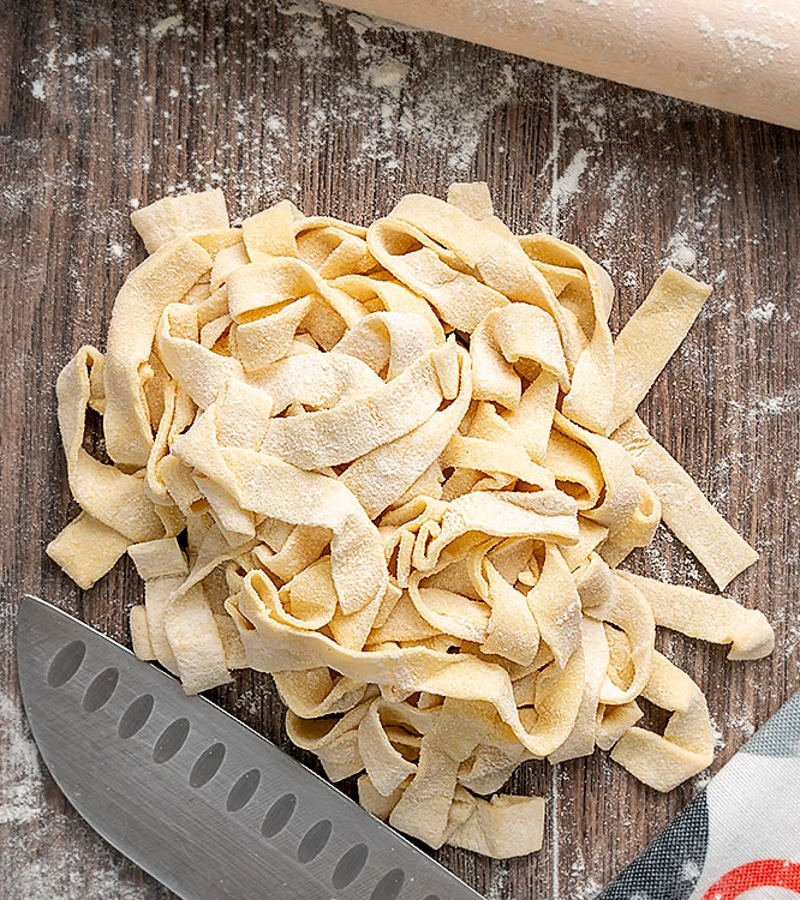 homemade pasta noodles on a brown board with a rolling pin and the blade of a knife