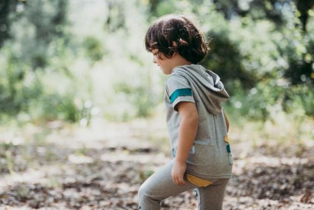Criança de lado, a andar num bosque, vestida com as roupas da marca Miss Castelinhos - cool clothes, cool kids.