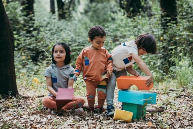 Três crianças, lado a lado, a brincar com blocos de construção, num bosque, e vestidas com as roupas da marca Miss Castelinhos - cool clothes, cool kids.