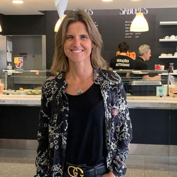"""Retrato de Filipa Pinto Coelho em primeiro plano. No fundo, o balcão do café, com dois funcionários atrás do balcão. Nas costas de um deles está visível a menção """"Gerações Autónomas""""."""