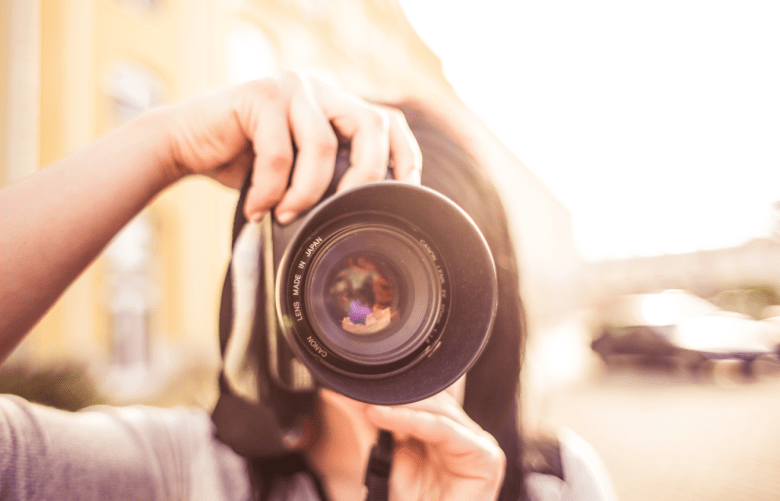 girl in grey sweater holding camera taking picture