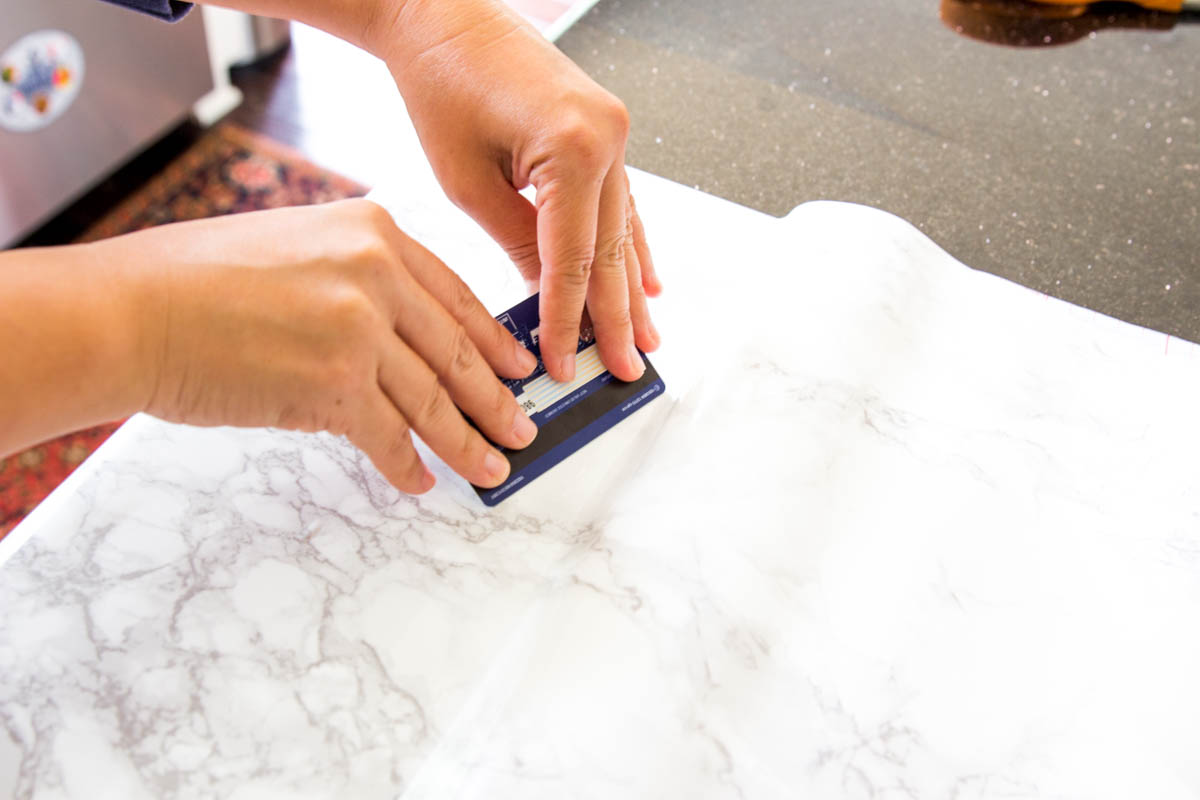using credit card to apply contact paper to kitchen countertops