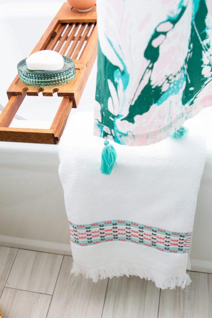 white bathroom blue and green glass tile Drew Barrymore flower line Walmart
