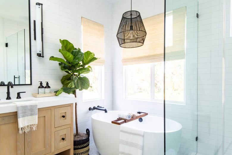 woven shades, black pendant, modern bathroom, free standing tub, oak vanity, black fixtures