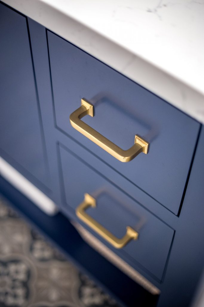 quartz countertop, blue vanity, brass hardware