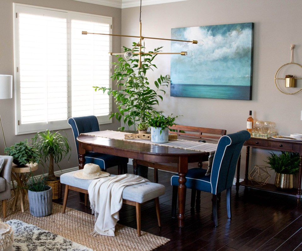 Dark wood dining area, adjacent to grey couch seating area