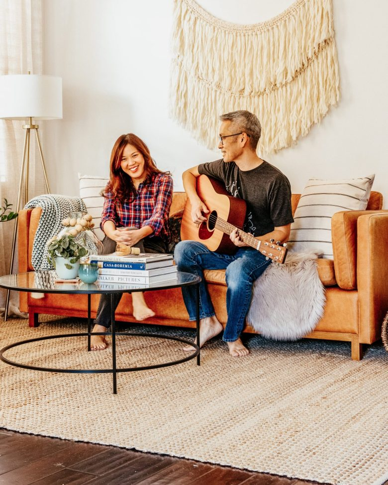 Travis serenades Anita with a guitar on the couch