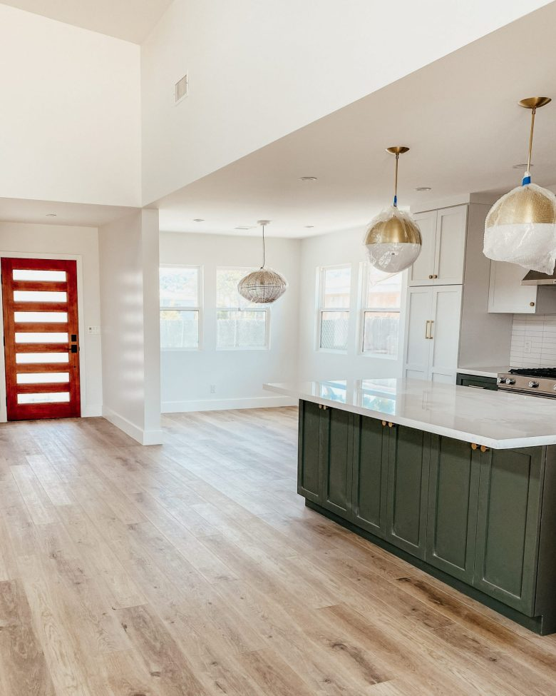 The open kitchen space with kitchen island, breakfast nook, and front door in view