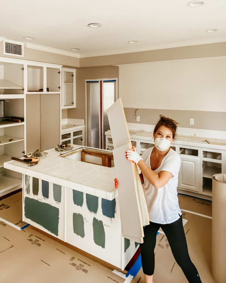 Anita demoing the kitchen, with blue and green swatches painted on the kitchen island