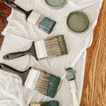 Paintbrushes dipped in varying shades of muted green