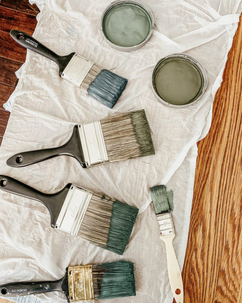 Paintbrushes dipped in varying shades of muted blues and green