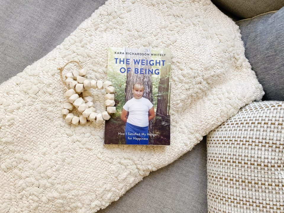Book 'The Weight of Being' laid on a blanket with mandala beads