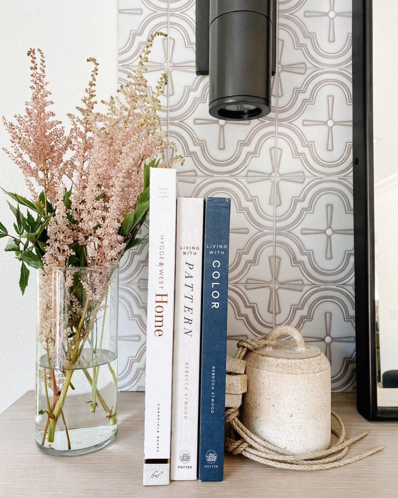Books arranged on the mantle with flower arrangement and soft, patterned tile