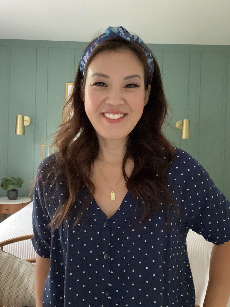 Anita in a blue polkadot top against her green bedroom board & batten