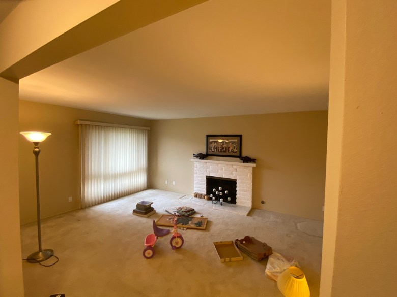 photo of the old living room with carpet and a white fireplace