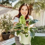 Anita in the backyard, holding out a plant