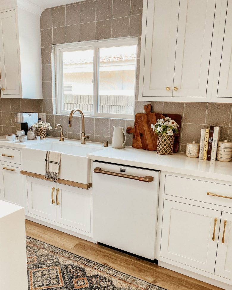 white shaker style cabinets with gold, faceted drawer pulls, and grey textured backsplash