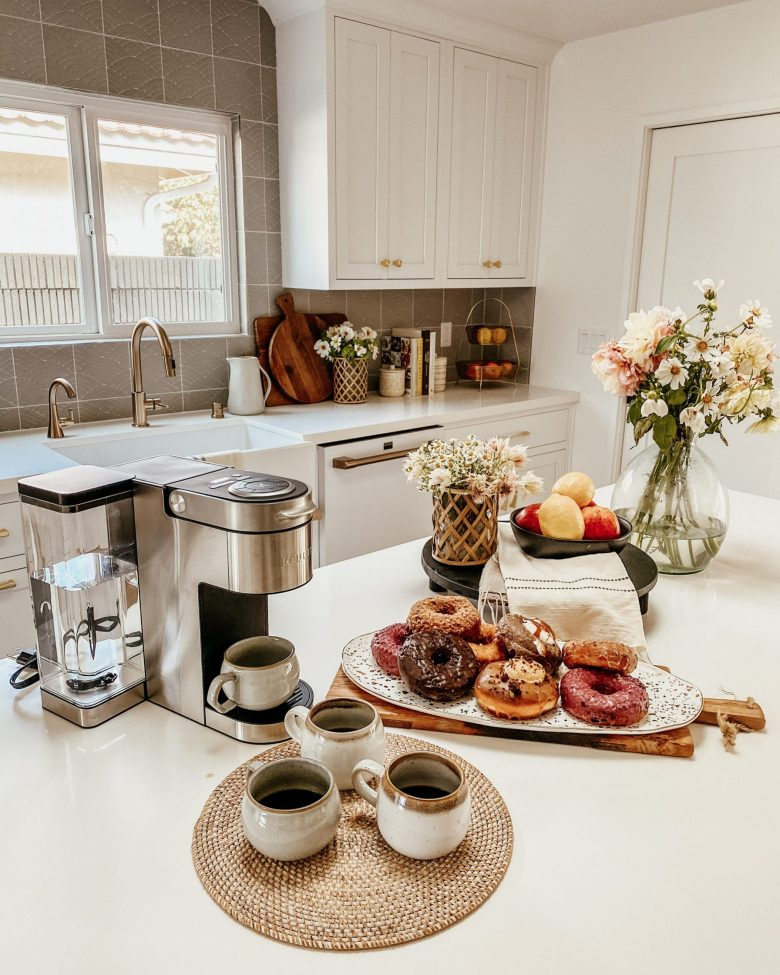 coffee and donut spread on a clean, white, modern counter
