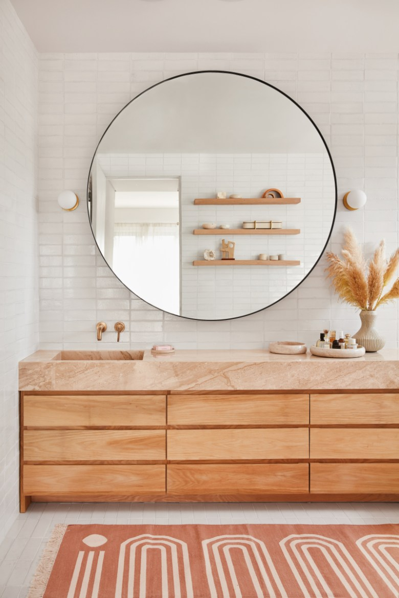 Natural earthen counter set atop wooden vanity with large round mirror backed by white fireclay tile