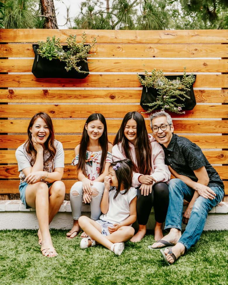 The Yokota family smiles in the back yard of their home