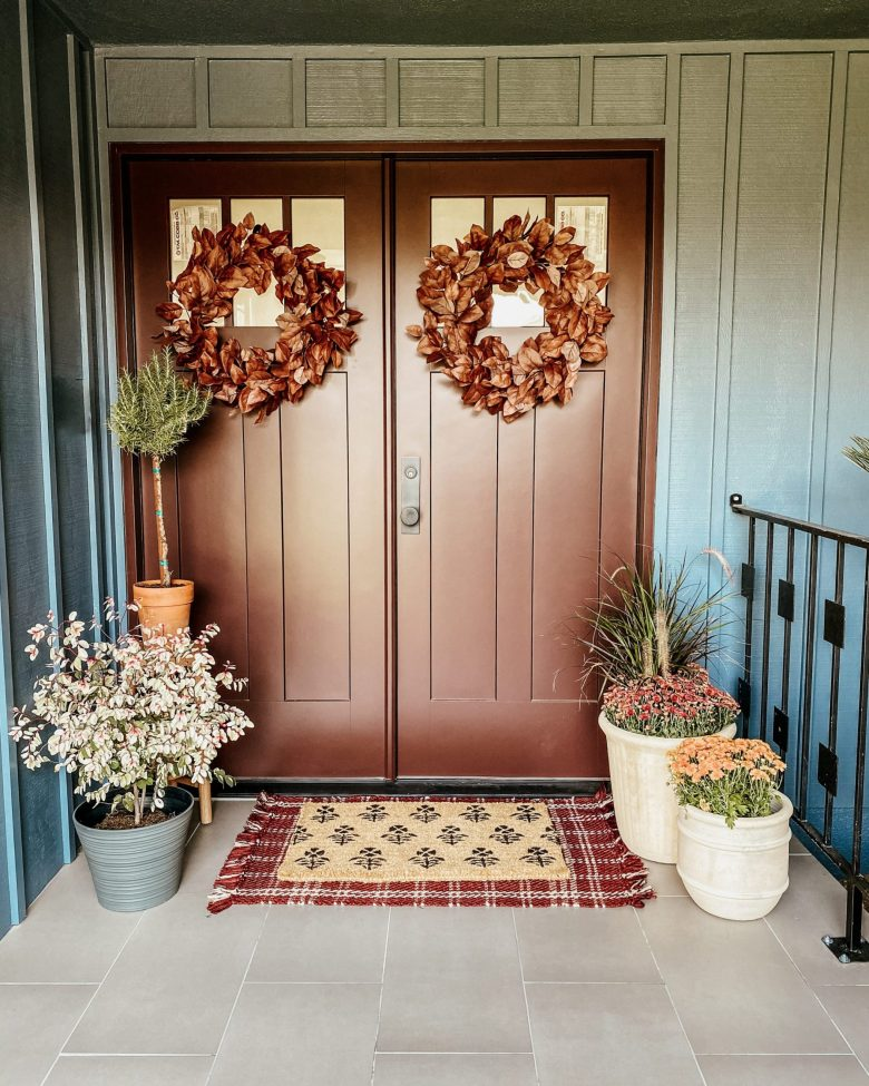 The door is a lovely bronze, highlighted by the surrounding plants and fall wreaths