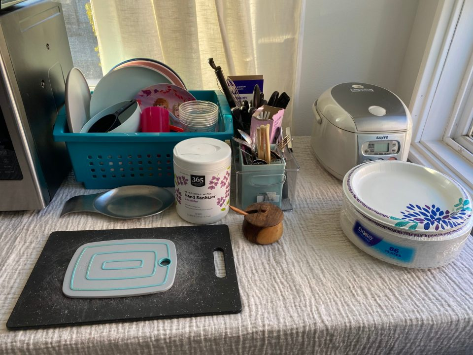 Our makeshift kitchen countertop includes dishes, cutting boards, and sanitizing wipes