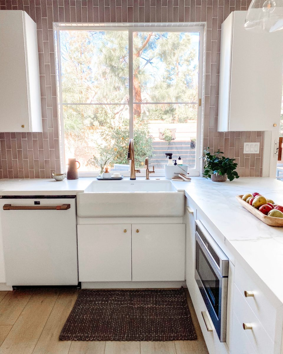 A white farmhouse sink below a bright window set in white marble with a brass Delta faucet