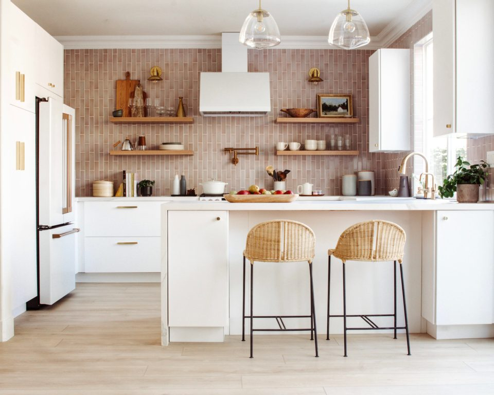 The full kitchen in view, with two pendant lighting over the peninsula and small sconces illuminating open shelving