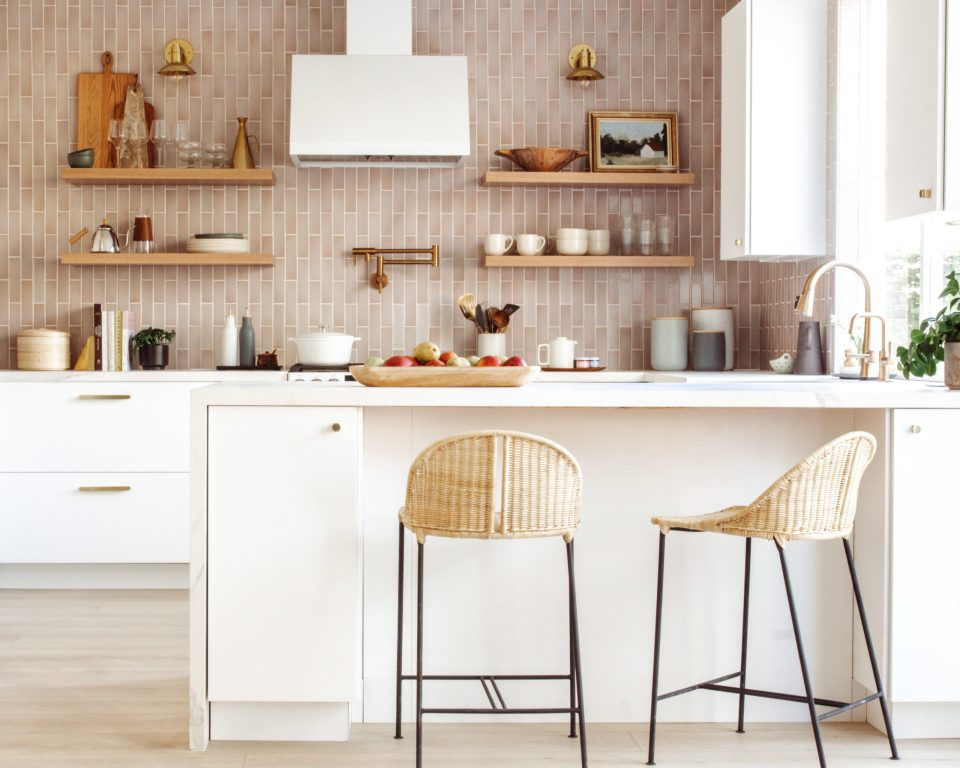 A holistic look at the modern kitchen, with mauve tile, white cabinets and countertops, and wooden and rattan accents.