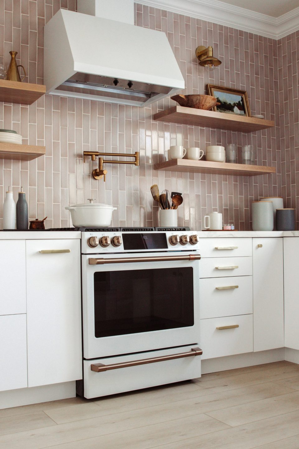 A white stove set in white modular cabinets with brass hardware against mauve backsplash that goes all the way to the ceiling!