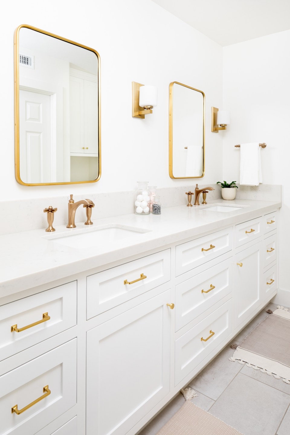 Bright white cabinets and countertops are accented by brass faucets, fixtures, sconces, and mirrors